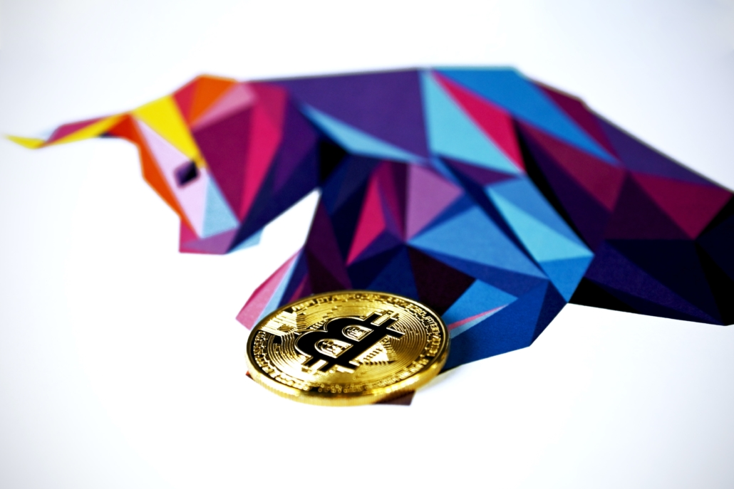 Bitcoin with a bull in the background emblematic of cryptoassets